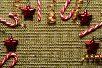 Frame for greeting card from Christmas decorations: stars, candy, ribbons and more. On a green background