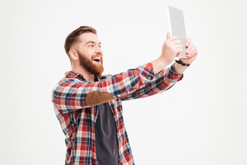 Cheerful bearded man making selfie photo on tablet computer