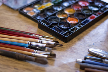 Used paint brushes on the table at artist's atelier