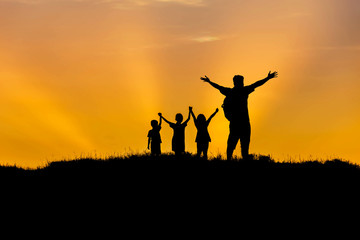 Silhouette father  and children standing raised hands up on sunset  happy time family concept