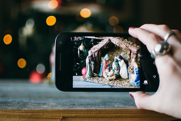 person takes photo of Christmas Manger scene with figurines including Jesus, Mary, Joseph, sheep and magi.