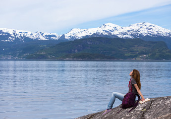 girl reading on a fjord coast