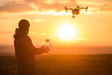man playing with the drone. silhouette against the sunset sky