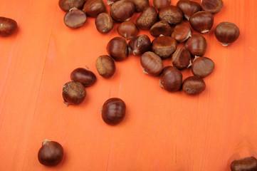 raw chestnuts on  orange wooden background