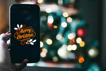 person takes a photo on a smartphone of merry christmas with a christmas background