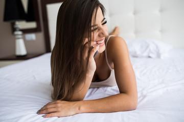 Beautiful girl speak phone in the bed