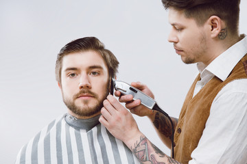 Attractive barber doing beard form