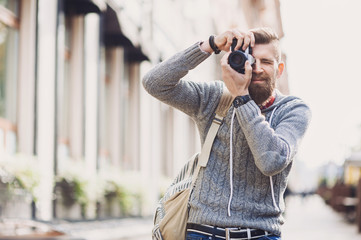 Young cheerful man photographer takes images with camera outdoors. Travel and active lifestyle concept