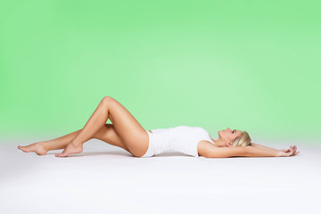 Young and fit blond woman posing in white lingerie