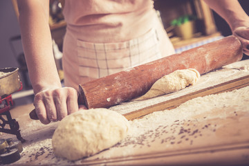 Close up of female baker hands kneading dough and making bread with a rolling pin. Retro look.