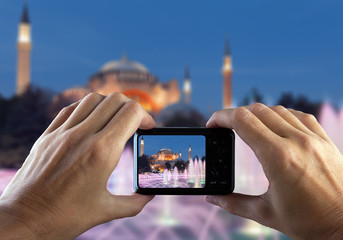 Travel concept. Hands making photo of night city with smartphone camera. Istanbul at sunset. Turkey