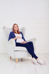 Young pregnant woman sitting on chair wearing casual comfortable