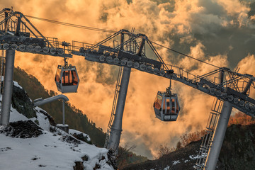 Cableway lift gondola cabins on cloudy mountain sunset background beautiful winter scenic landscape