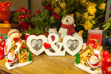 Two Heart shaped photo frame on wood tableAgainst the background of Christmas toys