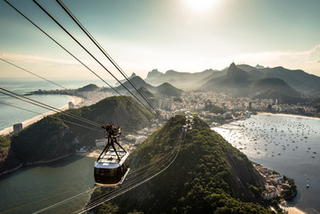 Fototapete - View of Rio de Janeiro city from the Sugarloaf Mountain by sunset with a cable car approaching
