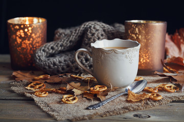Autumn leaves, hot steaming cup of coffee and a warm scarf