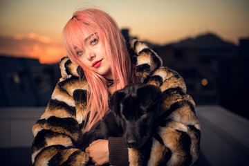 Cute woman and her pet dog posing at the top of a building at sunset
