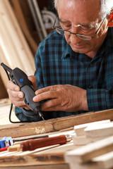 Senior carpenter carving wood with engraver tool. Restoring the old furniture.