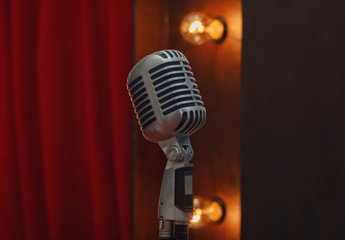 Retro microphone on stand on the background of red curtain. Musi