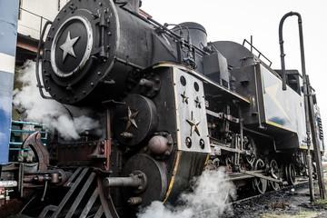 Old steam engine locomotive train and smoke at Ooty trains station, Nilgiri Mountain Railway, India