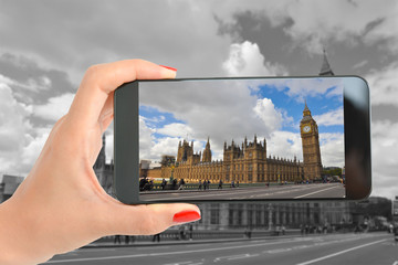 Woman taking a picture with smartphone at Big Ben and the Palace of Westminster, London
