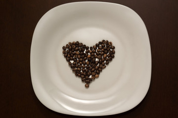 coffee beans in the shape of a heart on a plate
