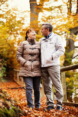 Senior couple enjoying fall  in the forest.