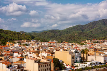 Aerial view of European town on a natural hills with many bars, hotels and restaurants in sunny day with blue sky. Tossa De Mar, Costa Brava, Spain.