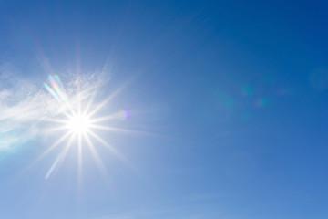 Lens flare from rising sun against blue sky