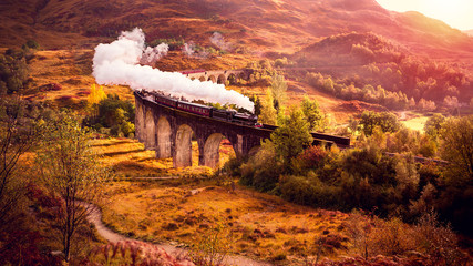 Eine Dampflockomotive fährt über das Glenfiann Viaduct