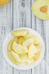 Portion of Honeydew Melon on wooden background (selective focus)
