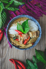 Thai Green Curry with Pork on Thai Fabric and  Old Wooden Backgr