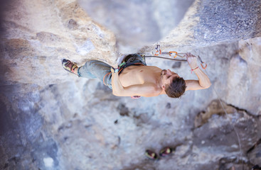 Male rock climber clipping rope, view from above