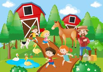 Many children and farmer in the farmyard