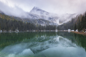 Lake Valagola and snowcapped mountains covered with clouds, Italy