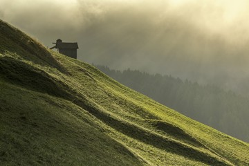 Dawn light rays on meadows of Sesto in Pustertal, South Tyrol, Italy