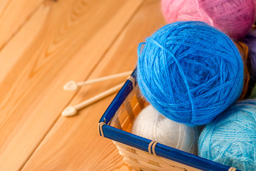 colored yarn for knitting in the basket on wooden boards