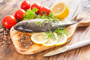 fish with a lemon and tomatoes on a table, selective focus