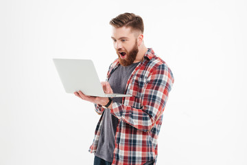 Excited bearded man looking at laptop