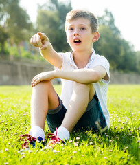russian boy sitting grass surprise pointing away