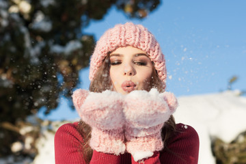 Beautiful young woman blowing snowflakes