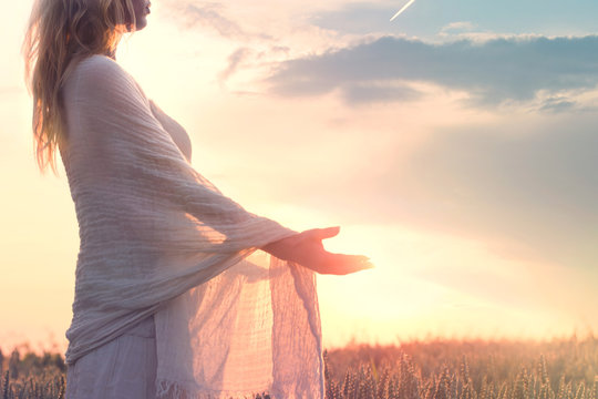 dreamy woman holding the sun in her hands