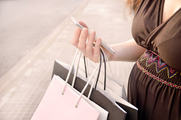 pregnant woman with shopping bags using smartphone