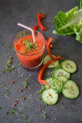 Superfood, roter Smoothie aus Paprika, Tomaten und Salatgurke, Hintergrund schwarzer Schiefer, mit kleinen roten getrockneten Beeren, Gurkenscheiben, Salatblatt und roter Paprika,  Textfreiraum