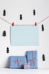 Christmas background mock up with handcrafted presents in white, red, black, and blue colors.