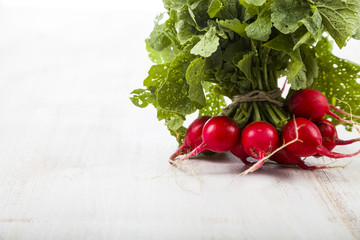 Ripe red radish with leaves on a wooden table close-up. Fresh ve