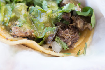 Beef and pork street tacos with garnishings, including onions, chives, salsa, red peppers