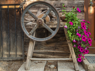 old grindstone with crank and flowers