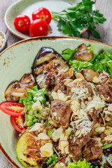 Hot salad with veal, mushrooms, salad leaves, eggplant, zucchini, tomatoes, garnished with grated almonds and Parmesan cheese and glass of wine on wooden background. Healthy food
