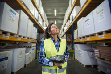 Puzzled woman in warehouse working with hand scanner and looking for one particular item. First in first out, Last in last out, team working together concept photo.